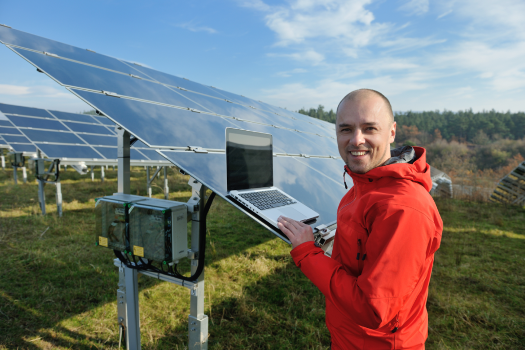 A man with a laptop stands in front of a solar panel array