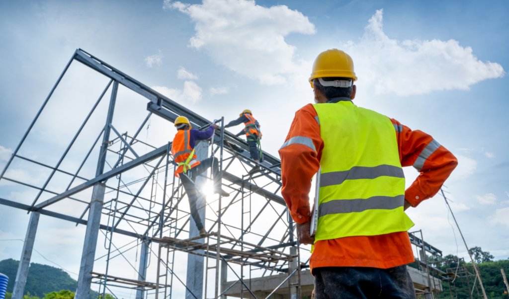 Men constructing a building as their supervisor watches