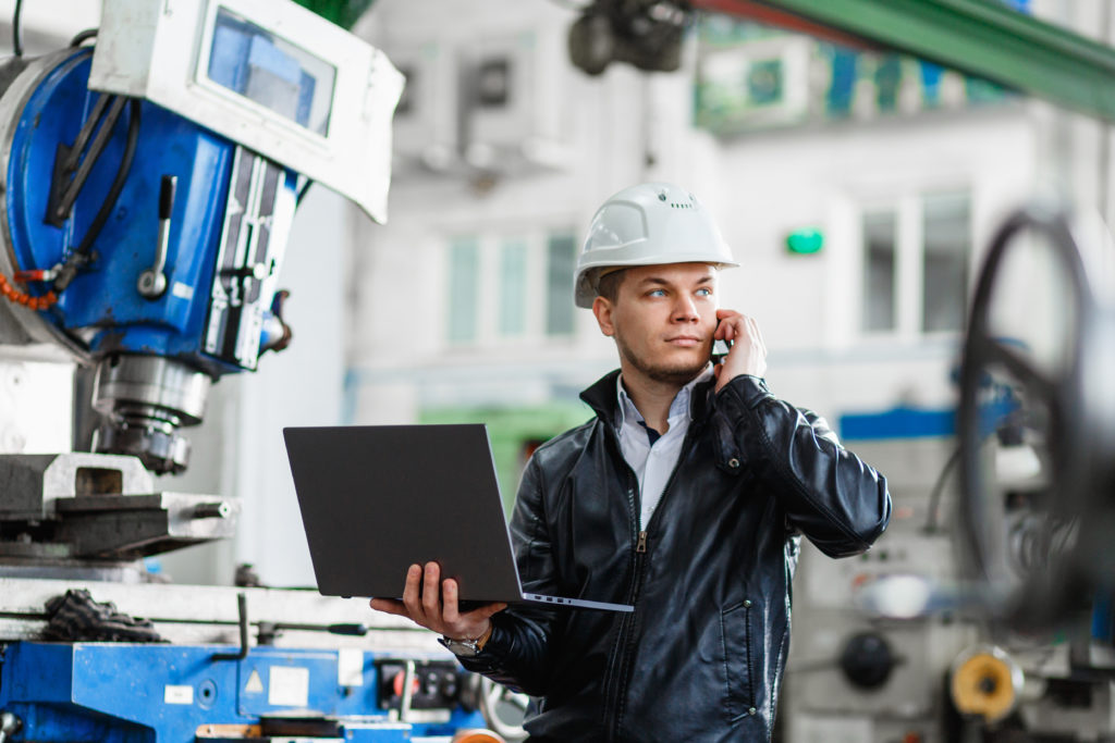 Man holding a laptop on the phone inside an industrial factory